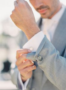The groom fastens the cuff exposing the cufflings